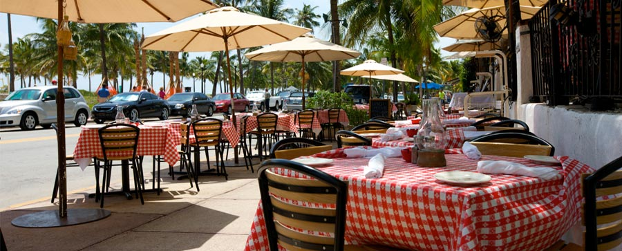 al fresco dining|tables and umbrellas, palm trees at Florida restuarant